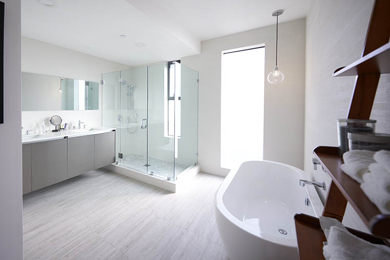 Modern domestic bathroom with shower cabin and freestanding bath, sunlight